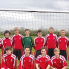 A football team wearing red in front of a goal post in Saffron Walden, Essex