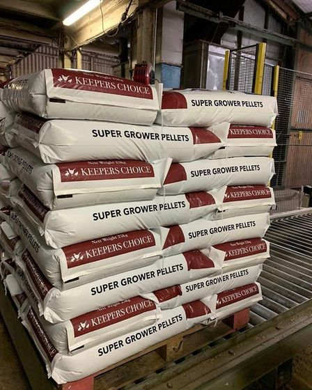 A stack of gamebird feed in bags on a pallet in a barn