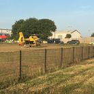 The East Anglian Air Ambulance, after landing at Barnards Meadow in Lowestoft, with police cars also at the scene.