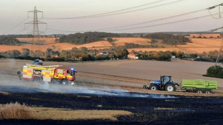 A charred field near Littlebury, Essex after a blaze. A fire engine and tractor