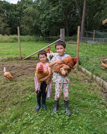 Ronnie, 6 and Dottie, 4 holding chickens at Waterways Farm in Norwich