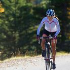An athletic woman enjoys an afternoon road bicycle ride on a sunny day.