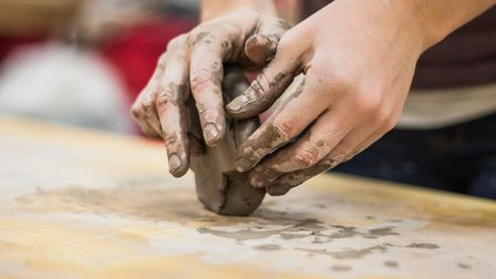 A pair of hands mould a lump of clay on a wooden table