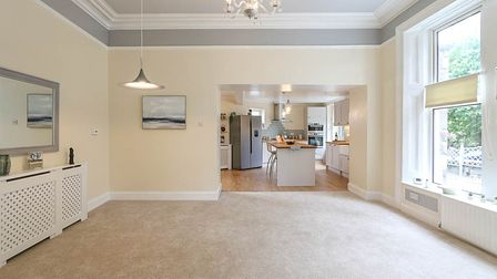 An empty dining room in the house in Stafford Place, Weston, with cream walls, beige carpet, window and door to kitchen