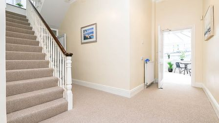 A hallway in the house in Stafford Place, Weston, with cream walls, white bannister staircase, beige carpet and door