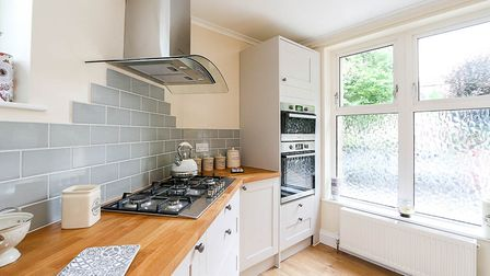 Bright kitchen in the house in Stafford Place, Weston, with double oven, gas hob, wooden worktops, grey tiles and cream units
