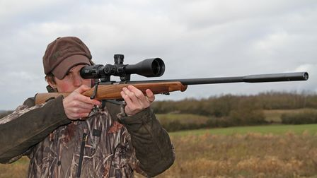 Young man shooting the Steyr Mannlicher Zephyr .22 LR free hand in a field