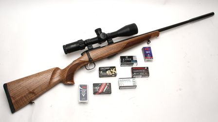 The Steyr Mannlicher Zephyr .22 LR on white background surrounded by boxes of ammunition