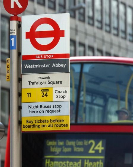 A number 24 bus arrives at the stop outside London's New Scotland Yard.