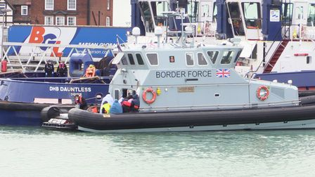 A group of people, thought to be migrants, waiting on a Border Force rib to come ashore at Dover mar