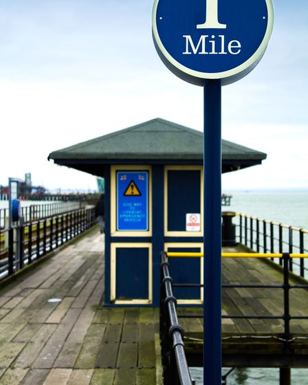 Blue sign from Southend Pleasure Pier showing you've reached 1 mile of its distance