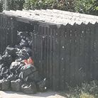 The communal bin store at Choristers Court, St Albans is overflowing with rotting rubbish bags blocking its entrance.