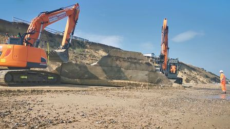Heavy plant machinery moving the concrete slabs into place at the base of the cliffs.