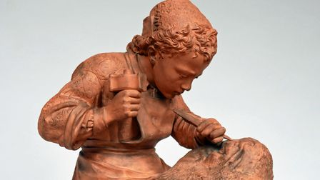A terracotta statuette after the renown sculpture by Emilio Zocchi of young Michelangelo sculpting the head of a faun.