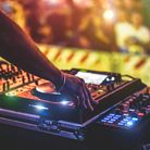 Dj mixing outdoor at new year party festival with crowd of people in background - Nightlife view of