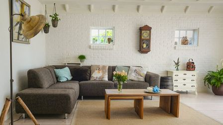 living room interior design with brown sofa, cushions and cream walls