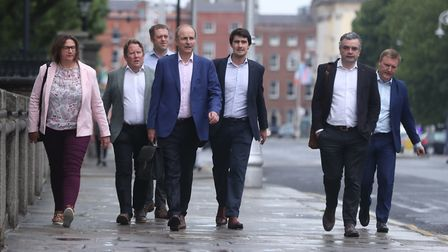 Fianna Fail leader Micheal Martin (centre) arrives at government buildings in Dublin to discuss outs