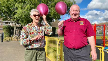 A man and woman stand side by side holding pink balloons in front of Golden Acre playground, Saffron Walden