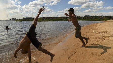 Children play by the shore of the Paraguay river in Asuncion. Photo: EITAN ABRAMOVICH/AFP via Getty