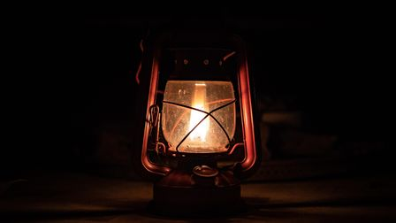 A lit lantern casts an unsettling glow, surrounded by the dark
