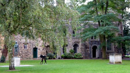 A grassy courtyard with a statue of Black Shuck prowling