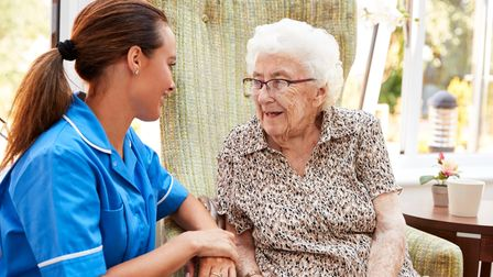 Senior woman sitting in a chair and talking with a nurse in a retirement home. Picture: Getty Images