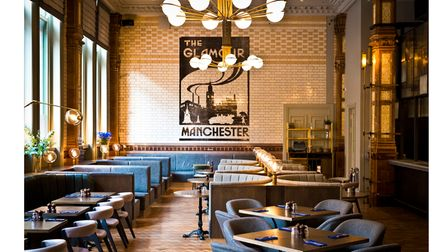 The dining room has a parquet floor, blue seating, a ball-glass chandelier and a wall painting of Manchester's skyline