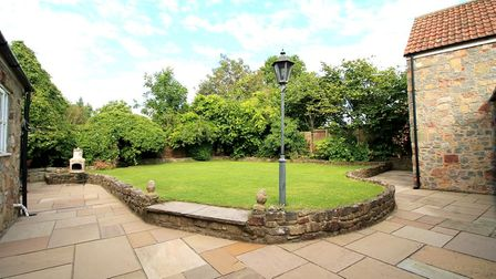 Semi-circular lawned garden with lampost, beige patio, and hedges, at the back of the cottage in North End Road, Yatton.