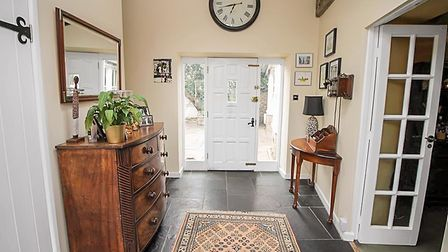 Hallway with slate floor tiles, runner, white door with glass side panels, clock above, cream walls and wooden furniture