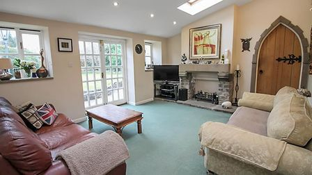Living room in the cottage in North End Road, Yatton, has a green carpet, double glazed doors and a stone fireplace.