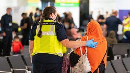 A member of Border Force staff with a female evacuee as refugees arrive from Afghanistan at Heathrow