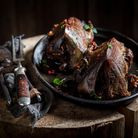 A dark roast pheasant on a log style table with a carving set to the left