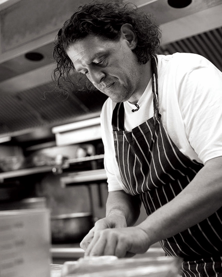 Chef Marco Pierre White chopping food; black and white photo