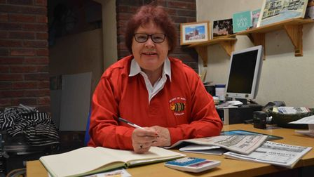 Phyllis Baxter dressed in red sat at her desk with a pen, book and other office equipment