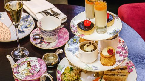 A selection of sweet treats and sandwiches adorn a tiered stand with matching teapots and cups plus champagne flutes