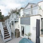 Modern white and grey render and glass exterior beach-house with external stairs and decking.