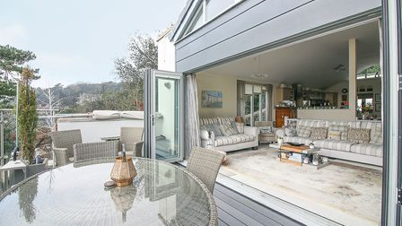 Open bi-folding doors with living area beyond and grey decking with garden furniture in front.