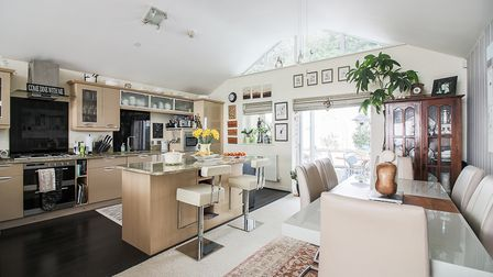Kitchen and dining area of an open-plan room with beige units including a breakfast bar, dining table and French doors