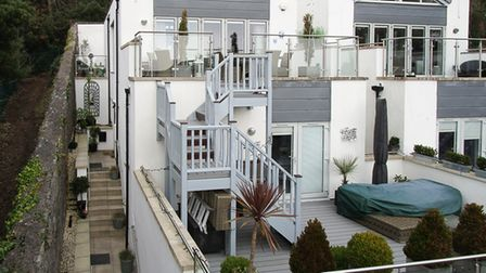 Front of the modern property in The View, Weston-super-Mare, is white and grey, with external staircase and glass balcony