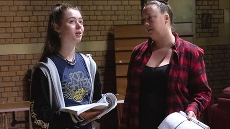 Two girls standing next to each other in a theatre holding scripts in their hands