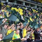The Norwich fans wave the flags that were put out on every seat before the Premier League match at C
