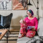 Yolandi at home pictured in pink sitting on her sofa with pen and notebook in hand