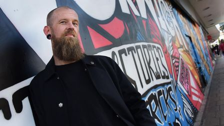 Graffiti artist and muralist, Andrew Wilson, with his work in St Stephens Street. Picture: DENISE BR