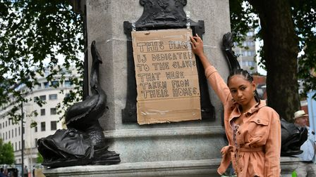 A Bristol protestor places her dedication on the empty plinth where the statue of Edward Colston in