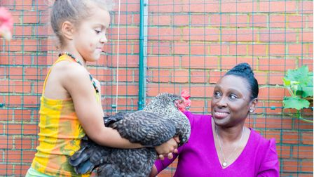 Cllr Anntoinette Bramble meets one of the school's chickens.