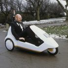 Sir Clive Sinclair demonstrating his C5 electric vehicle, the battery-come-pedal powered trike, at Alexandra Palace in 1985