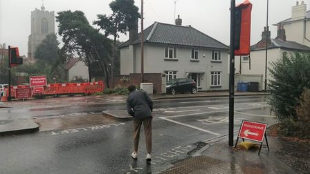 A man attempts to cross the road at Chapel Field North by edging out to see approaching cars