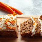 Carrot cake slices on wooden cutting board with whole carrots and walnuts in the background.