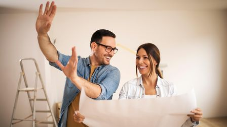 Young couple standing in their apartment holding blueprint
