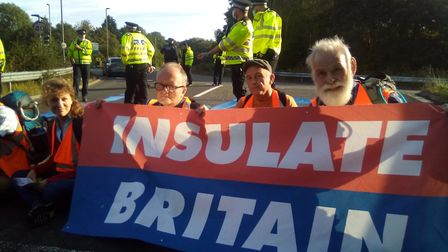 """Protestors block a slip road holding an """"Insulate Britain"""" banner"""